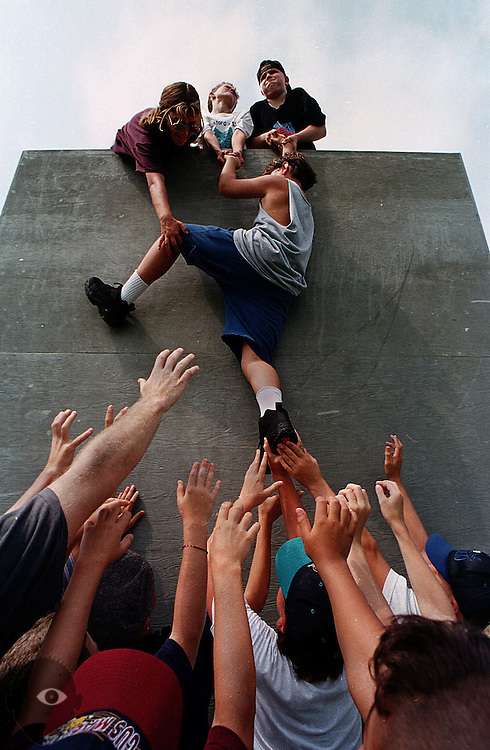 Camp attendees learn to work as a team to cross over a wall in preparation of their first rock climbing experience.