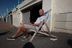 UK ENGLAND BRIGHTON 8SEP16 - Deckchair rental man Evan Raymond (36) of New Zealand takes it easy at the Brighton beach front.<br /> <br /> jre/Photo by Jiri Rezac<br /> <br /> &copy; Jiri Rezac 2016