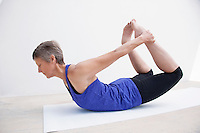 Fit seniro woman demonstrating basic asanas and chair yoga.
