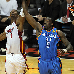 Jun 19, 2012; Miami, FL, USA; Miami Heat power forward Chris Bosh (1) and Oklahoma City Thunder center Kendrick Perkins (5) battle for a rebound during the first quarter in game four in the 2012 NBA Finals at the American Airlines Arena. Mandatory Credit: Derick E. Hingle-US PRESSWIRE