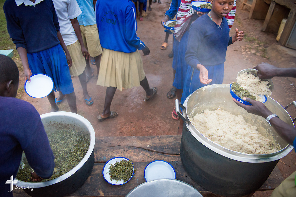 Young men and women at the U-Dom ELCK (Evangelical Lutheran Church in Kenya) Project 24 gather for a dinner of ugali and greens on Wednesday, June 22, 2016, in Chepareria, Kenya.  LCMS Communications/Erik M. Lunsford