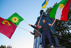 London, October 11th 2014. Thousands of protesters from the UK's Kurdish community demonstrate in London against the delay in assisting the people of the Syrian city of Kobane in their fight against ISIS. They also accuse Turkey, with whom the Kurds have had a long-running insurgency of siding with the Islamic State by doing nothing to help Kurds in Kobane. PICTURED: Protesters stand on the plinth of Churchill's statue in Parliament Square.