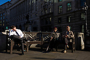 A businessman dozes in autumn sunshine with an elderly couple in Bank triangle in the City of London. A scene of both the pressures of a modern job in a capital city and also the years of leisure after a lifetime's career, after which a pension secures a healthy future, we see two generations - of the modern work era alongside retirement.