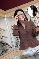 Happy mid adult woman trying on glasses while looking into hand mirror