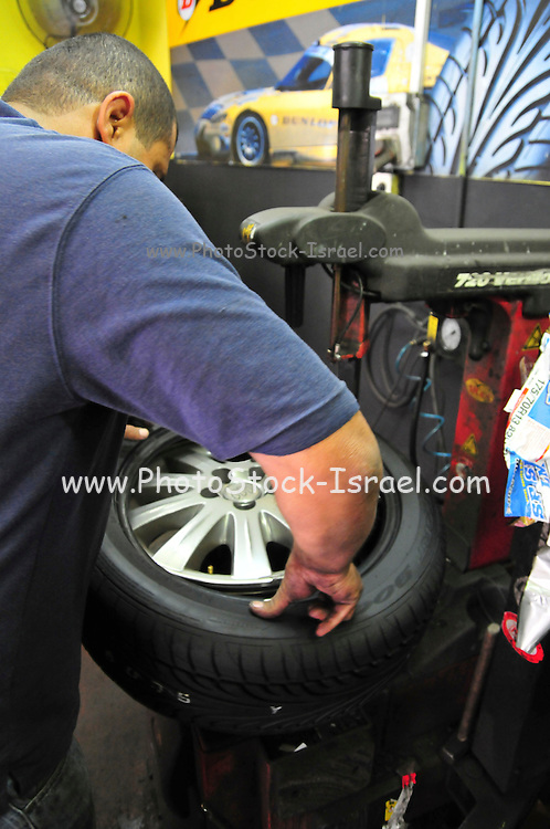 Mechanic replaces a new tyre on the wheel