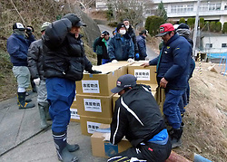 London News Pictures. 20/03/2011. Villagers hold emergency ration boxes down to prevent them being blown away by the downdraft from the delivery helicopter's rotors in Onagawa, Japan. Thousands are missing after a 9.0 magnitude strong earthquake struck on March 11 off the coast of Japan causing a tsunami wave. Photo credit should read Alex Tee/London News Pictures