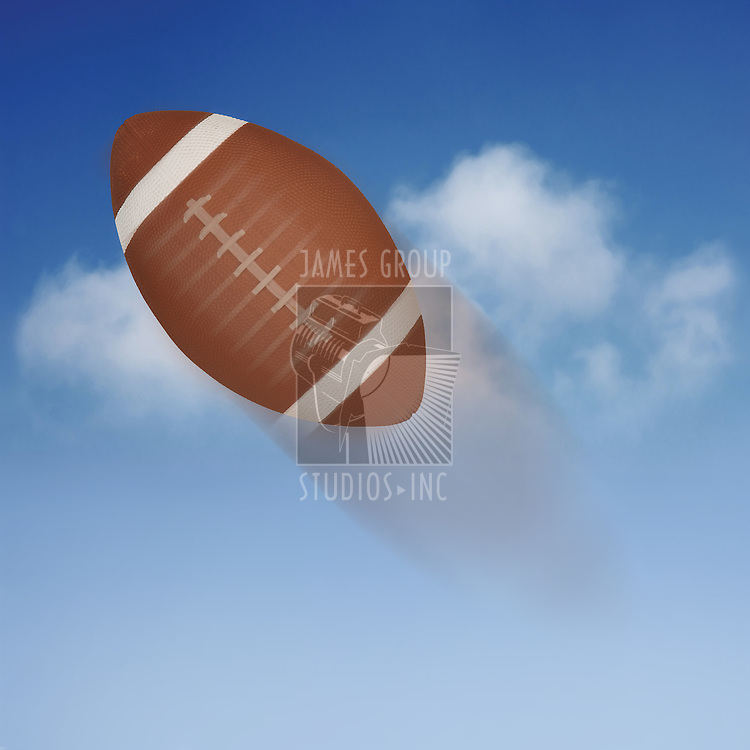 American football soaring through the air against a blue sky with motion blur