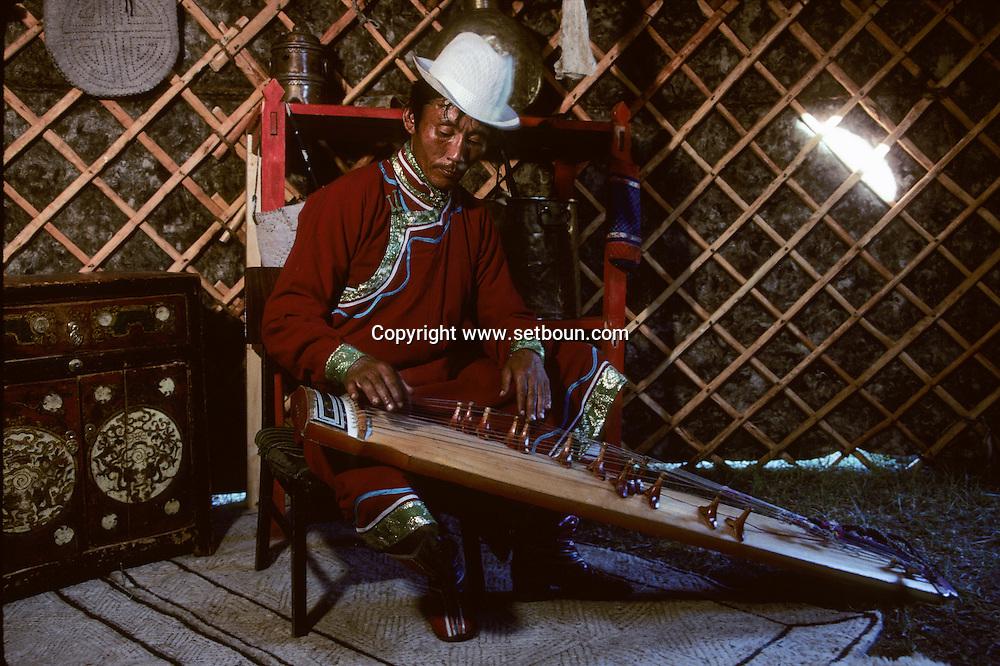 Mongolia.traditional music  Hoit  Tsanher Aguy      / musique traditionnelle,(Sum de Mangan, dans aymag de Qovd, Mongolie).   Musicien à la yatag dans une yourte. La yatag est une cithare oblongue à chevalets mobiles, diffusée dans l'Asie du Sud et d'Extrême Orient. On la rencontre aussi bien au Viétnâm sous le nom de dan tran, qu'en Chine (zheng), qu'en Corée (kayakeum), qu'au Japon (koto). Malheureusement, les Mongols ont délaissé depuis de nombreuses années la fabrication de cet instrument et, sous le nom de yatag, on trouve pratiquement toujours des kayakeum importées de Corée, avec leurs treize cordes en soie.