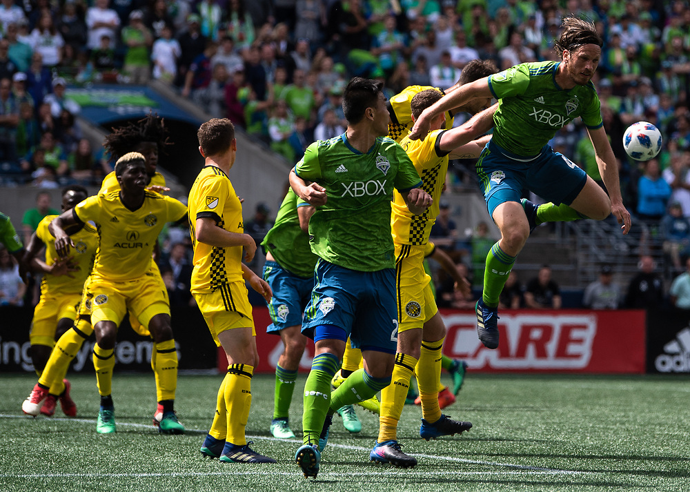 May 05, 2018; Seattle, Washington, US;  Seattle Sounders defender Gustav Svensson (4) gets some air as he battles for the ball during in action between the Seattle Sounders FC and Columbus Crew at Century Link Field. Photo credit: Rick May - Rick May Photography