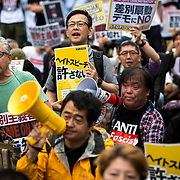 KAWASAKI, JAPAN - JUNE 05: Anti-fascist and anti-racist groups with placards block several racist group from disrupting an counter-racist protest in Nakahara Peace Park, Kawasaki City, Kanagawa prefecture, Japan on June 5, 2016. A district court in Kanagawa Prefecture has issued a first-ever provisional injunction preventing an anti-Korean activist from holding a rally near the premises of a group that supports ethnic Korean people.<br /> <br /> Photo: Richard Atrero de Guzman