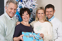 Senior couple and mid adult couple in front of Christmas tree, portrait
