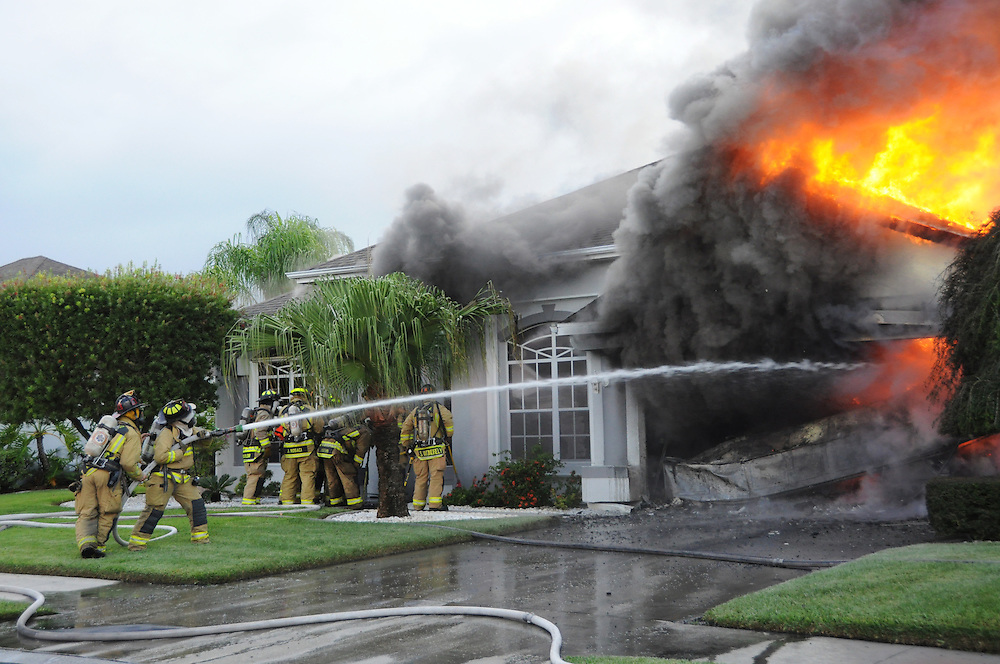 Andrew Knapp, FLORIDA TODAY -- July 27, 2011 -- Firefighters battle a fire Wednesday evening at a house on Carriage Hill Road in Suntree.