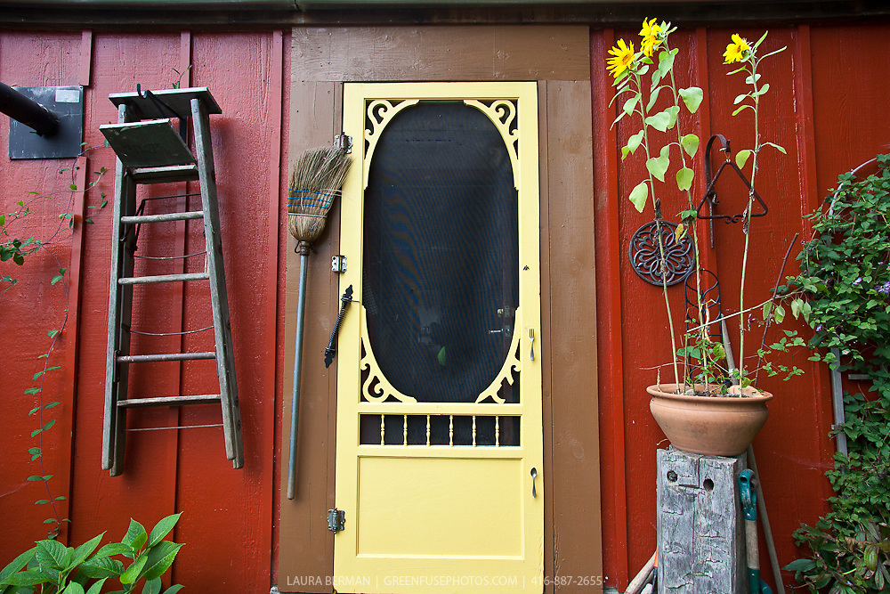 Yellow screen door on a red farmhouse.