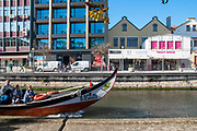 Tourists on a colourful boat (moliceiro) on a canal in Aveiro, Portugal