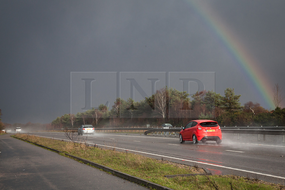 © Licensed to London News Pictures. 03/01/2014. A31, Near Ringwood, New Forest, Hampshire, UK. A rainbow forms over the A31 as dark clouds and heavy rain pass over the New Forest near Ringwood in Hampshire, UK. More wet and windy weather along with the risk of flooding is forecast for much of the south and south west of England & Wales over the weekend. Photo credit : Rob Arnold/LNP