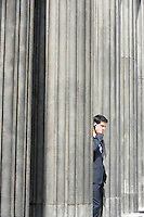 Businessman standing outside building between pillars on cell phone
