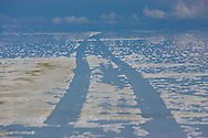 Vehicle tracks leave their mark  in the softened salt bed of the Salar de Uyuni in the rainy season in the Department of Potosi in Bolivia.