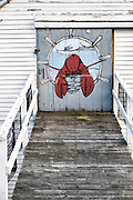 A mural of a lobster decorates the loading door of a boat house in the fishing community of New Harbor, Maine. The tiny picturesque pocket harbor is one of the last working harbors on the midcoast along the Pemaquid Peninsula