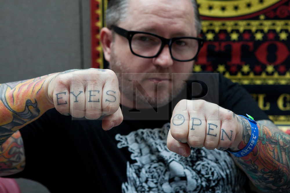 "© Licensed to London News Pictures. 28/09/2012. London, UK. A man shows off his ""eyes open"" knuckle tattoos. The 8th London Tattoo convention opened today, 28 September 2012 at Tobacco Dock in East London. The convention attracts tattoo artists and body art fans from all over the world and runs until 30 September 2012. Photo credit : Vickie Flores/LNP."