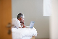 Man using laptop lying on stomach on bed