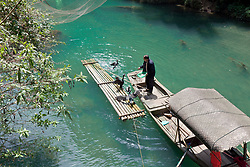 Man feeding tethered Cormorants, one of the living exhibits at a recreated Water Village, Hama Spring, Yangtze River. The birds catch fish for families and commercial interests but are unable to eat them because of a tight ring around their necks.  They are fed smaller fish that can slip pass that restriction.