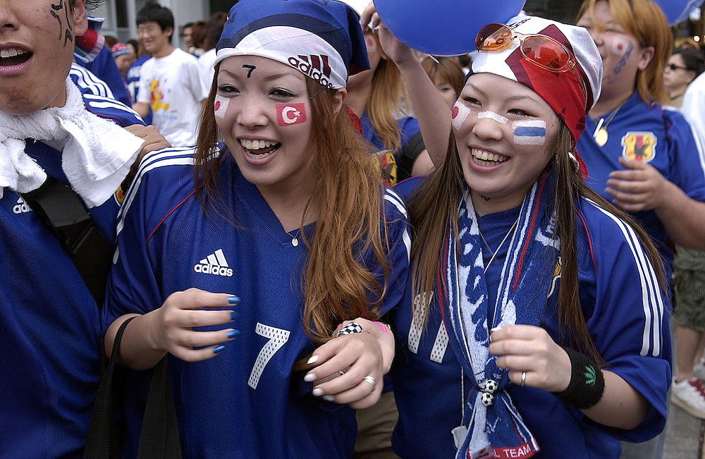 Female Soccer supporters wear Japan's team colours as a fashion statement in support of Japan's hosting the 2002 World Cup, Osaka Japan June 2002.©David Dare Parker/AsiaWorks Photography..©David Dare Parker/AsiaWorks Photography