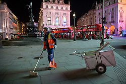 © Licensed to London News Pictures. 20/03/2020. London, UK. A street cleaner in front of Shaftesbury Memorial Fountain (Eros) in Piccadilly Circus. The West End was left unprecedentedly empty on Friday night following the government's announcement that all bars, pubs and restaurants must be closed immediately in the latest step to curb the coronavirus outbreak.  Photo credit: Guilhem Baker/LNP