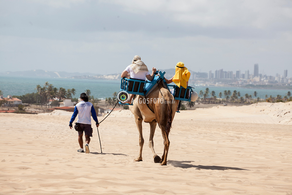 Casal passeando com dromedario no alto da Praia de Genipabu./ Couple walking in camel in Upper of Genipabu Beach. Rio Grande do Norte, Brasil - 2013.