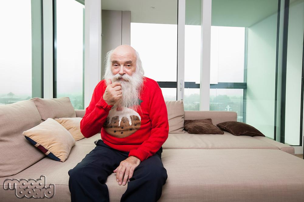 Portrait of thoughtful senior man sitting on sofa bed