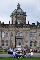 © Licensed to London News Pictures.22/08/15<br /> Castle Howard, North Yorkshire, UK. <br /> <br /> A man sits in front of his Rolls Royce enjoying a drink and a picnic as he and hundreds of other people attend the 25th anniversary of the Castle Howard Proms event near York. The theme of the event this year is a commemoration of the 75th anniversary of the Battle of Britain and the 70th anniversary of VE day and brings an evening of classic musical favourites celebrating Britishness to the lawns of Castle Howard.<br /> <br /> Photo credit : Ian Forsyth/LNP