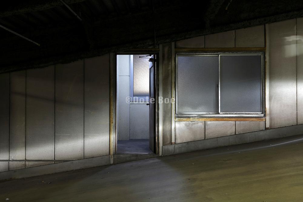 pedestrian door in a parking garage with head lights from a car