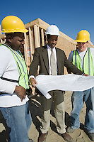 Two construction workers and surveyor studying blueprint