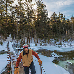 A man crosses a suspension bridge over the Hudson River near its source in New York's Adirondack Mountains. Upper Works Trail, East River Trail. Tahawus Tract, Newcomb, New York.