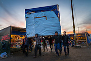 CALAIS, FRANCE - JAN 13: Refugees and volunteers work together to move makeshift shelters in the Calais refugee camp known as the 'Jungle' on January 13, 2016, ahead of the deadline given by the French authorities to clear the area within 100 metres of the highway.