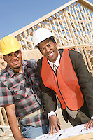 Architect and construction worker leaning to table with blueprints