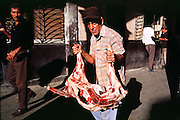 HAVANA, CUBA: A private butcher delivers a freshly slaughtered goat to a home in the central section of Havana, Cuba. Many staples, like bread, rice and meat are still rationed in Cuba. Cubans make up for the lack of government rations by shopping in private farmers? markets and government run dollar stores.  Photo by Jack Kurtz