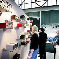 Nederland,Amsterdam ,30 september 2008..n de Amsterdam RAI begint dinsdag de Woonbeurs Amsterdam. De inmiddels zestiende editie duurt tot en met 5 oktober. De beurs toont aan de hand van verschillende sferen en stijlen wat de nieuwe trends voor de woninginrichting zijn. .Op de foto:.Bezoekers tijdens de Woonbeurs 2008 bekijken en bewonderen de retro radio's op en stand van  Tangent.