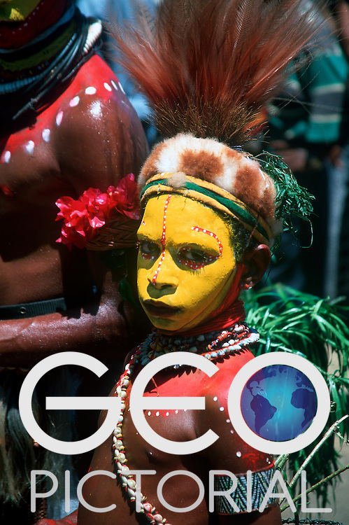 A young Huli wigman boy from the Southern Highlands in traditional costume at the Hiri Moale Festival..Port Moresby, Central Province, Papua New Guinea.