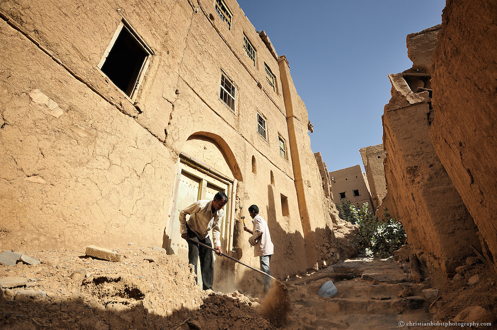 Bangldeshi workers break up a door of an abandoned mud building in  Al Hamra, Oman, 2011