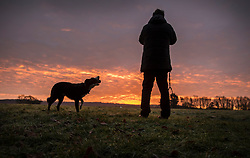 © Licensed to London News Pictures. 17/12/2017. Buckinghamshire, UK. A man takes a photograph of a stunning sunrise in Buckinghamshire as his dog looks on. Photo credit: Peter Macdiarmid/LNP