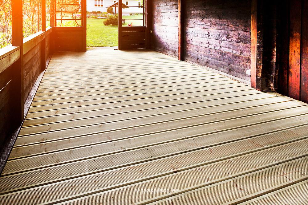 Rural wooden balcony in Estonia. New floor, painted, oiled walls. Doorway.