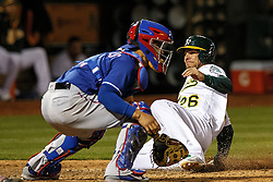 OAKLAND, CA - JUNE 14:  Danny Valencia #26 of the Oakland Athletics scores a run past Robinson Chirinos #61 of the Texas Rangers during the sixth inning at the Oakland Coliseum on June 14, 2016 in Oakland, California. (Photo by Jason O. Watson/Getty Images) *** Local Caption *** Danny Valencia; Robinson Chirinos