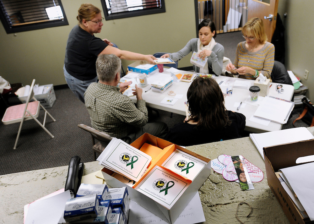 In this Friday, Feb. 22, 2013 photo, un-addressed postcards with green ribbons, foreground, sit in a box waiting for personalized messages to be written on them by the Newtown Volunteer Task Force in Newtown, Conn.  Volunteers are creating an archive of all the condolences and letters of support that arrived after December's massacre at Sandy Hook Elementary School, while other volunteers are saying thank you, one handwritten note at a time. Town officials estimate they received more than 175,000 letters and cards from around the world, many containing artwork or the thoughts of school children. (AP Photo/Jessica Hill)