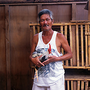 THE PHILIPPINES (Boracay). 2009. Galo Hechanova, 63 with his game cock before the cockfighting at the Boracay Cockpit,  Boracay Island. Photo Tim Clayton <br /> <br /> Cockfighting, or Sabong as it is know in the Philippines is big business, a multi billion dollar industry, overshadowing Basketball as the number one sport in the country. It is estimated over 5 million Roosters will fight in the smalltime pits and full-blown arenas in a calendar year. TV stations are devoted to the sport where fights can be seen every night of the week while The Philippine economy benefits by more than $1 billion a year from breeding farms employment, selling feed and drugs and of course betting on the fights...As one of the worlds oldest spectator sports dating back 6000 years in Persia (now Iran) and first mentioned in fourth century Greek Texts. It is still practiced in many countries today, particularly in south and Central America and parts of Asia. Cockfighting is now illegal in the USA after Louisiana becoming the final state to outlaw cockfighting in August this year. This has led to an influx of American breeders into the Philippines with these breeders supplying most of the best fighting cocks, with prices for quality blood lines selling from PHP 8000 pesos (US $160) to as high as PHP 120,000 Pesos (US $2400)..