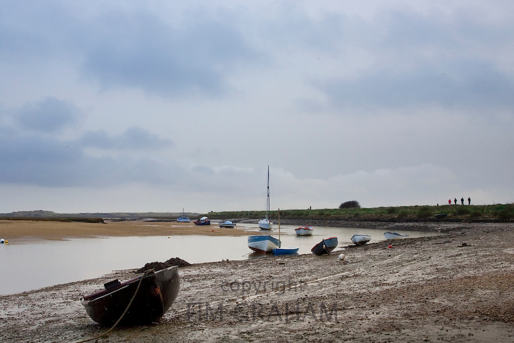 Small boats stuck in the mud at low tide in Overy Staithe, Norfolk, East Anglia, Eastern England, United Kingdom