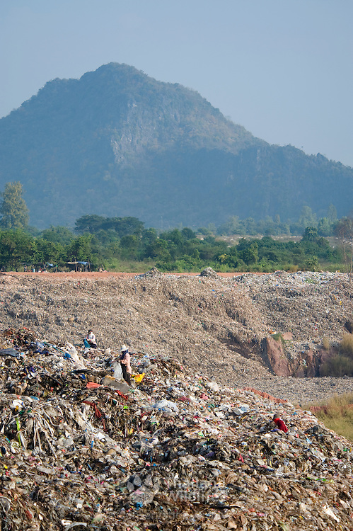 A mountain of wate at a landfill site in Thailand with a natural mountain as a back drop.