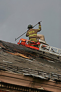 A fireman helps put out the last remnants of the fire on the roof of the Historic Eastern Market.