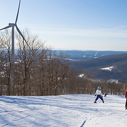 Skiers at Jiminy Peak ski resort in the Berkshire Mountains in Hancock, Massachusetts.  Wind turbine.