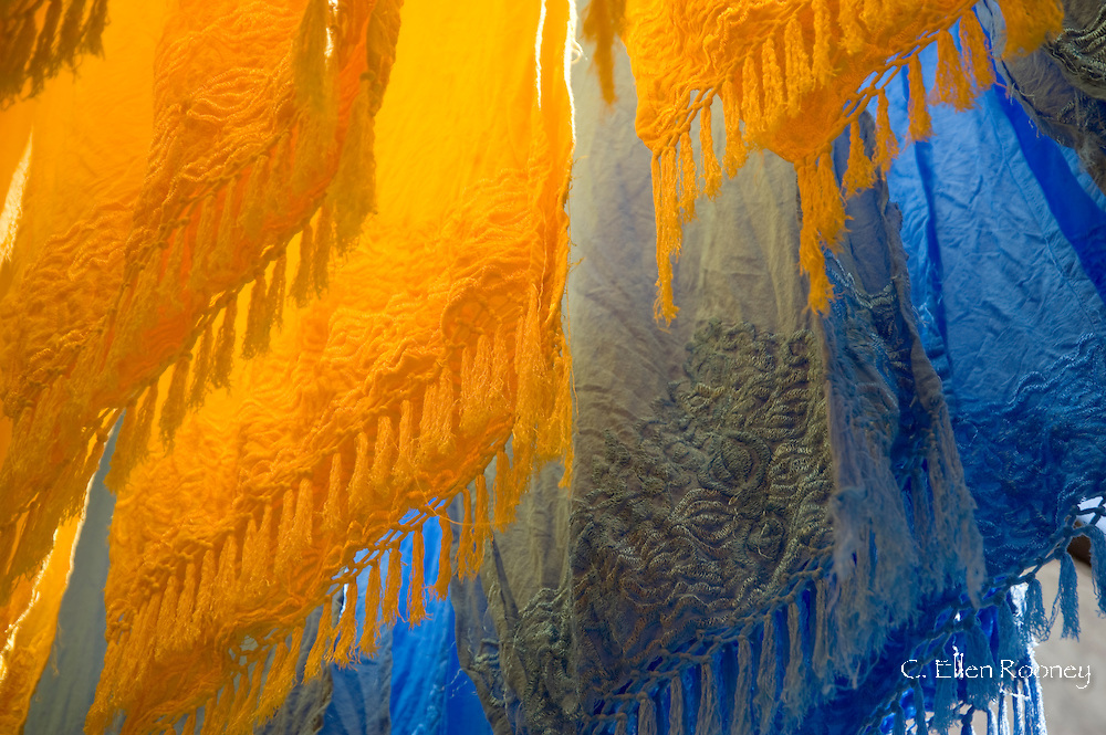 Brightly coloured dyed fabrics hanging to dry in the dyers souk, Marrakech, Morocco