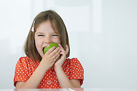 Girl (5-6) biting green apple